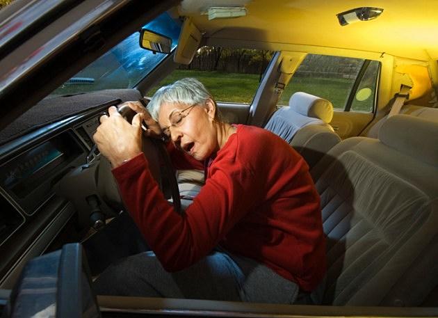 Woman asleep on steering wheel of car