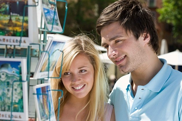 Smiling couple looking at postcards