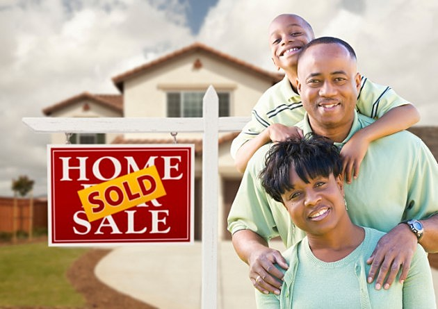 African American family in front of house and sold sign