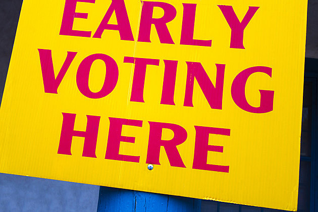 "Bright yellow ""EARLY VOTING HERE"" sign."